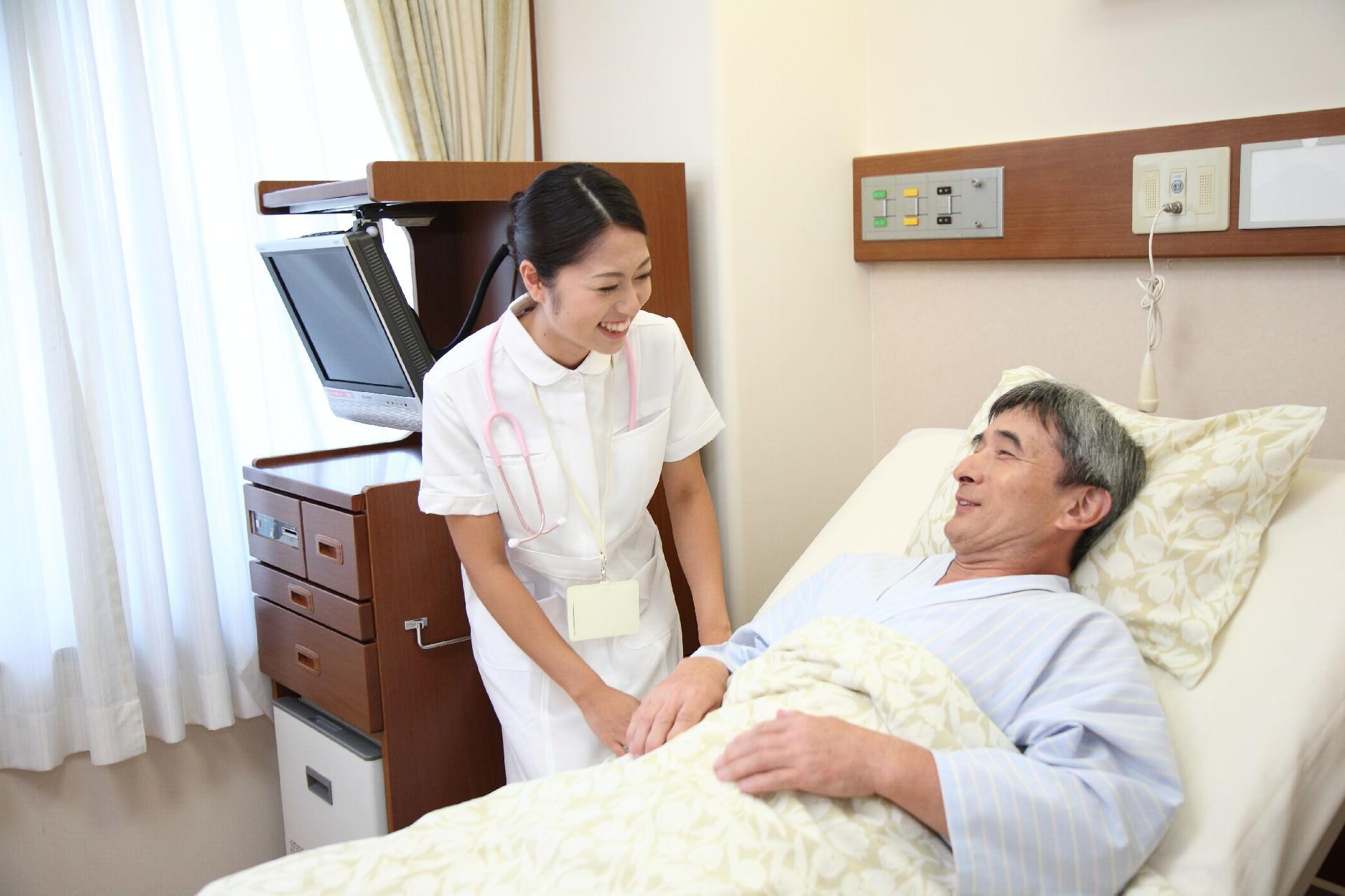 介護を受けるベッドで寝たきりの男性
