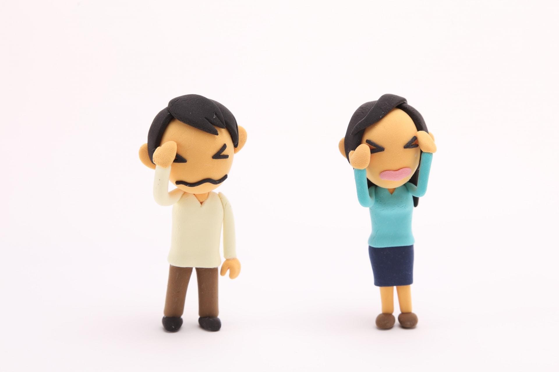 頭を押さえる男女の人形
