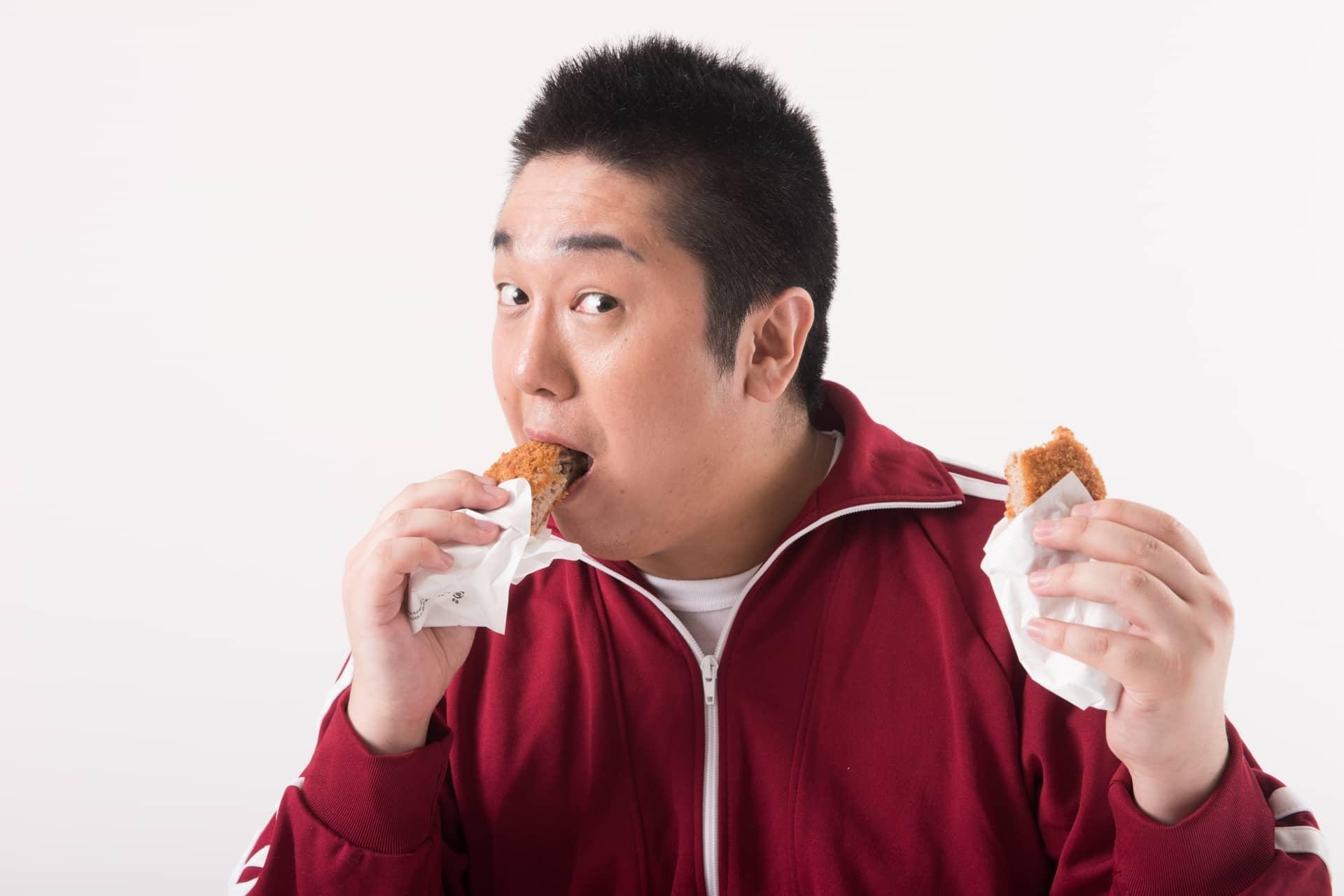 揚げ物を食べる男性