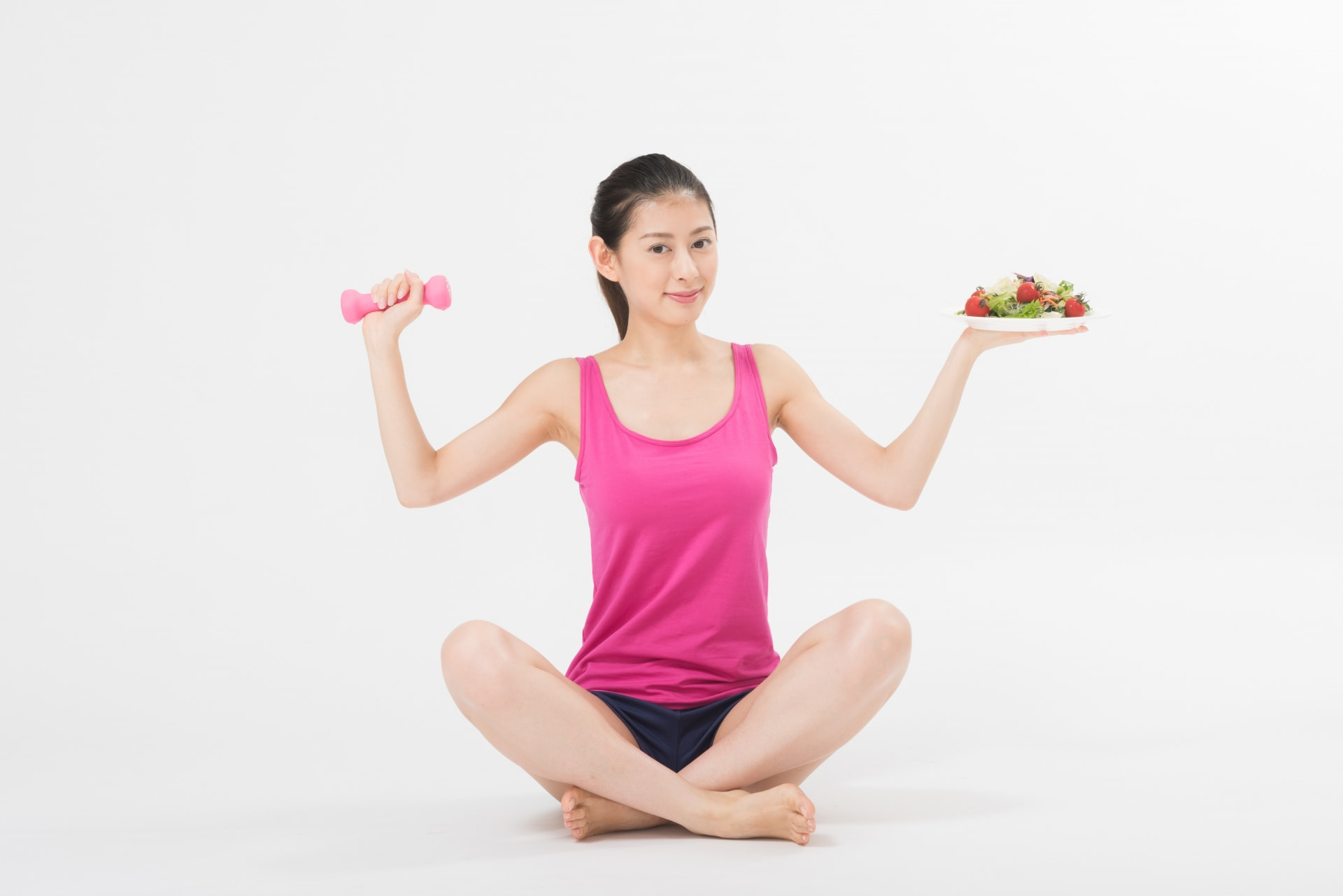 ダンベルと野菜を持つ女性