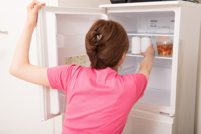 冷蔵庫の缶に手を伸ばす女性