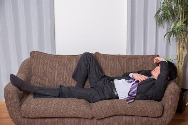 酔っぱらってソファーに寝る男性