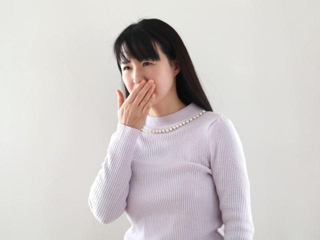 口元を抑える女性