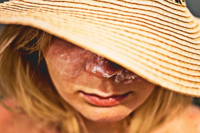 麦わら帽子で顔を隠す女性