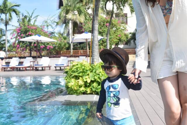 サングラスをかけてプールサイドを歩く男の子